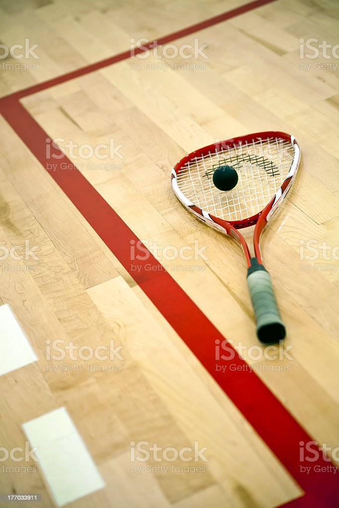 A squash racket on a court with a ball stock photo