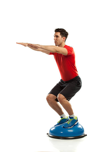 squat exercise on ball stock photo