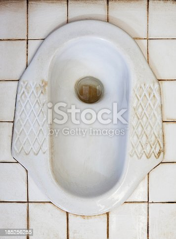 Grungy squat toilet set on white tiles. This kind of toilet is common in Asia.