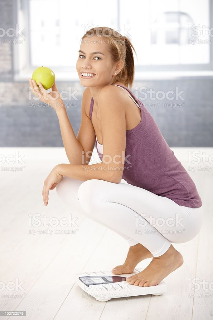 Squatter girl on scale holding apple royalty-free stock photo