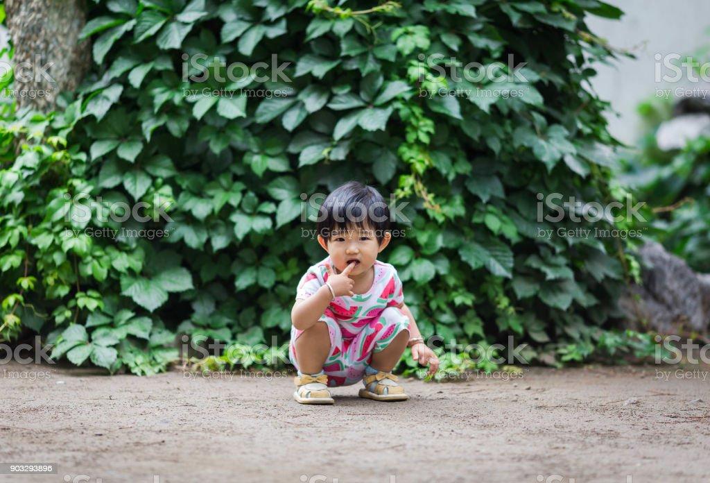 Accroupie doigt bébé sucer sur le plancher - Photo