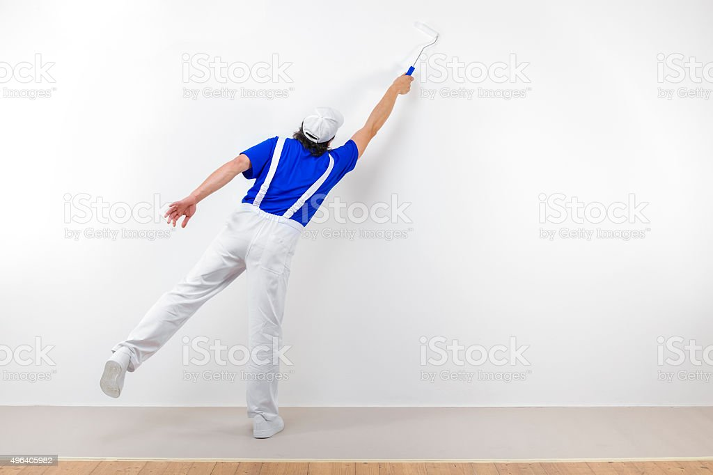 Squatting painter with paintroller on white wall stock photo