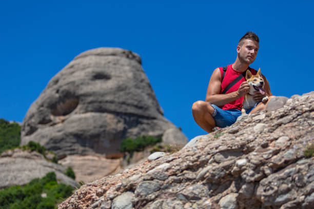 A squatting young man and his dog at the top of Montserrat mountain, Barcelona stock photo