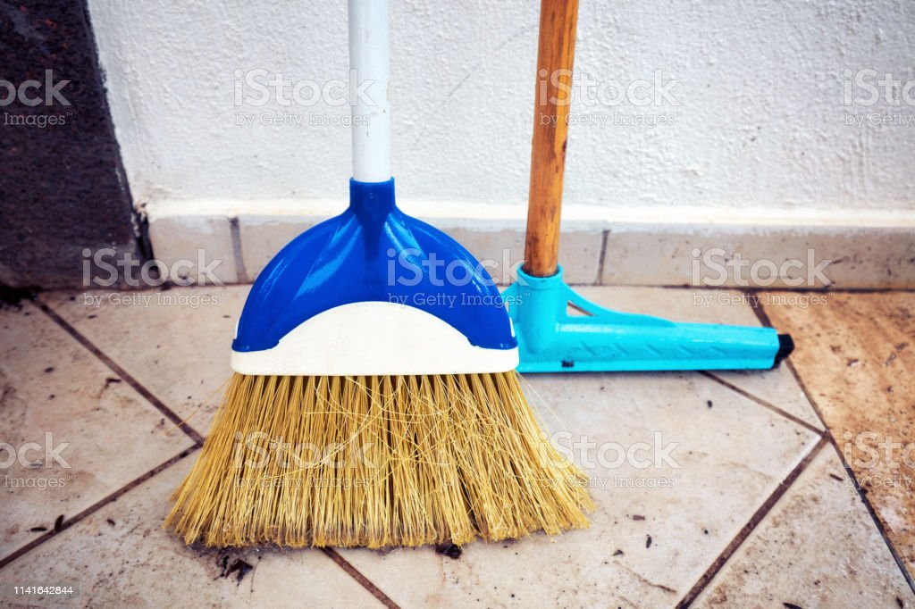 Squeegee Mop And Sweeping Broom Aligned To The Wall And Standing On The  Tiled Floor Of The Patio Of An House Stock Photo - Download Image Now