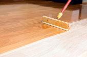 istock Squeegee Style Brush Applying Clear Polyurethane to Hardwood Floor 183771871