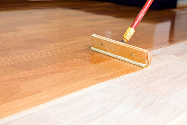 Squeegee Style Brush Applying Clear Polyurethane to Hardwood Floor stock photo