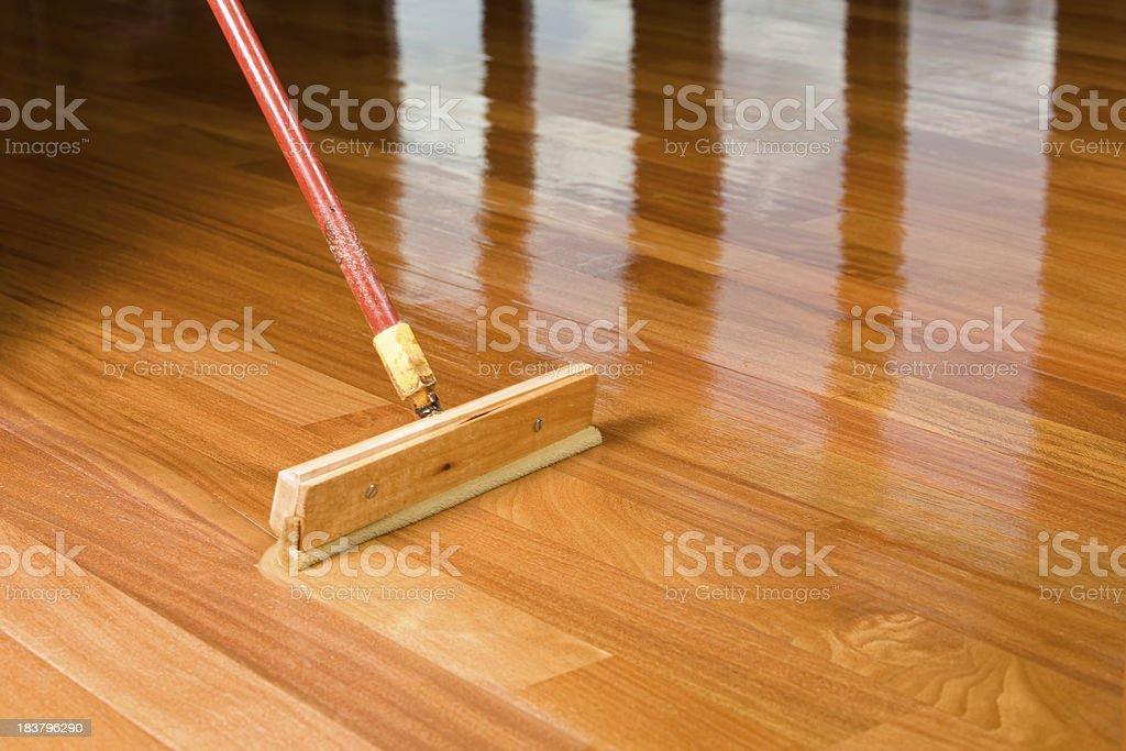 Squeegee Style Brush Applying Clear Polyurethane to Hardwood Floor stock photo
