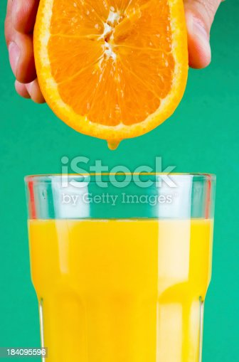 Juice from an orange dripping down in a filled glass of orange juice.