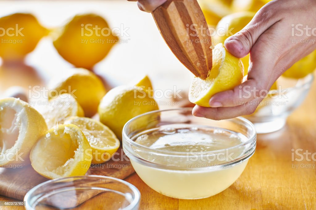 squeezing fresh lemon juice with wooden reamer into bowl royalty free stockfoto
