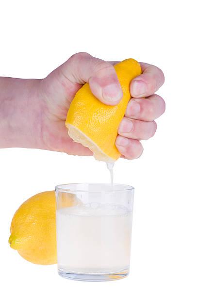 Squeezing lemon on white bacground stock photo