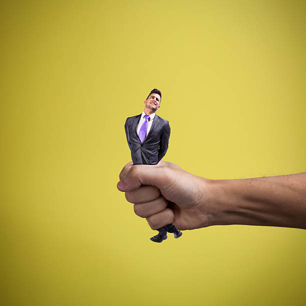 squeezing the businessman - squeezing stock pictures, royalty-free photos & images