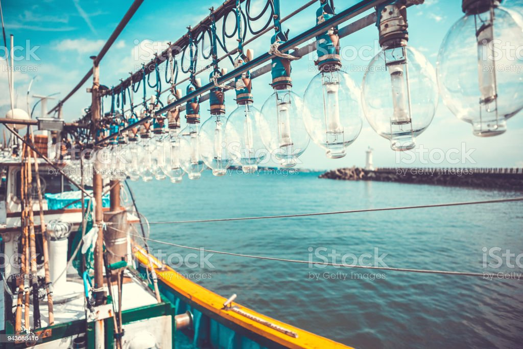 Squid fishing boat early in the moring in a small port - Jeju island, Korea stock photo