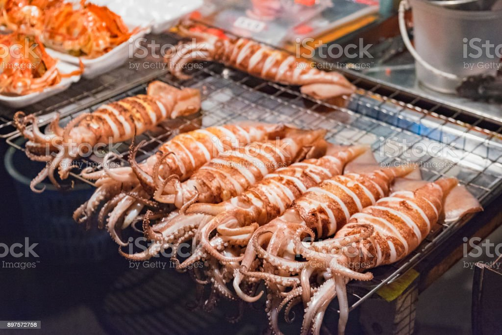 Squid on skewers is being grilled by a street vendor stock photo