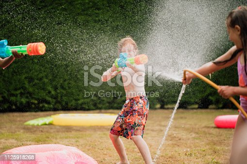 A front view shot of young children in a garden, they are having fun together enjoying a water fight with a garden hose and colorful water guns.