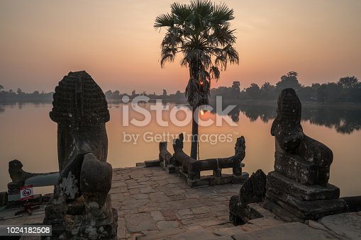 Sra Srang terrace in Angkor Wat temple complex, Cambodia. No people, sun rising on the lake horizon, view of terrace and statues of lions. No people