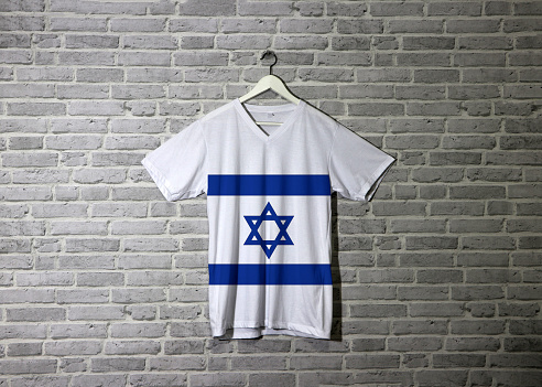 srael flag on shirt and hanging on the wall with brick pattern wallpaper.
