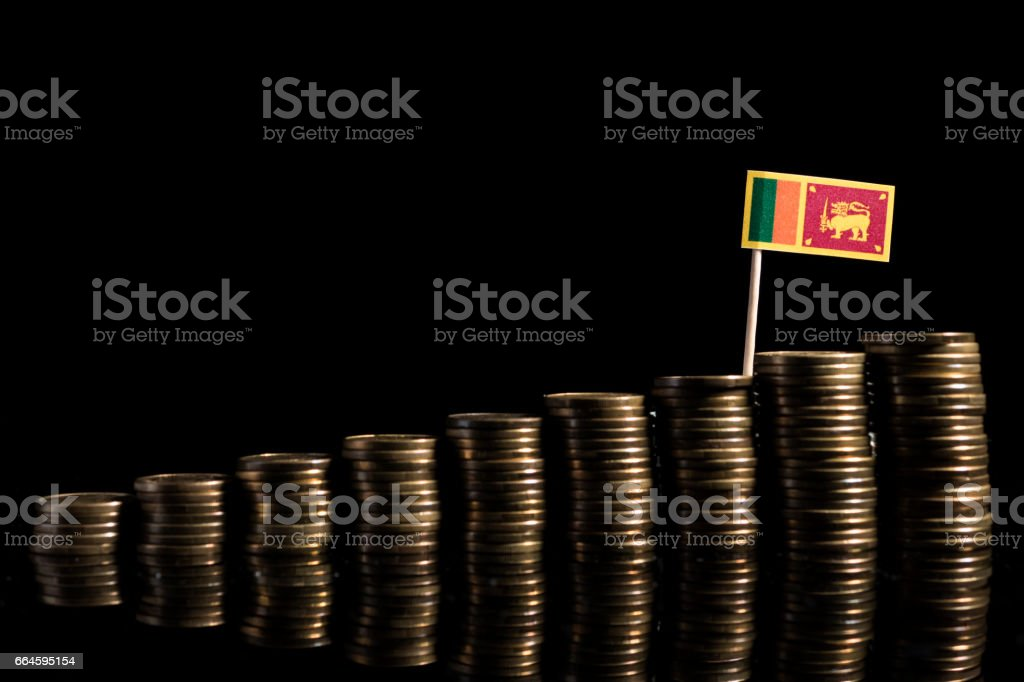 Sri Lankan flag with lot of coins isolated on black background stock photo