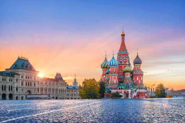 St. Basil's Cathedral and golden first rays of the sun St. Basil's Cathedral on Red Square in Moscow and golden clouds with the first rays of the autumn sun moscow russia stock pictures, royalty-free photos & images