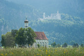 Church of Saint Coloman and castle of Neuschwanstein in the background. In the bavarian alps near the city of Fuessen, Germany. The castle was build in the 19th century by the bavarian king Ludwig and is on of the most visited monuments in Germany.