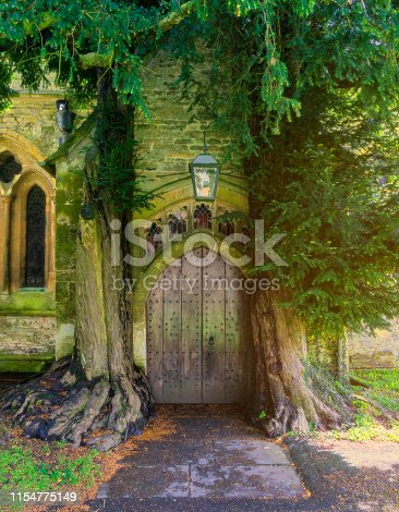 An old English village church door with yew trees