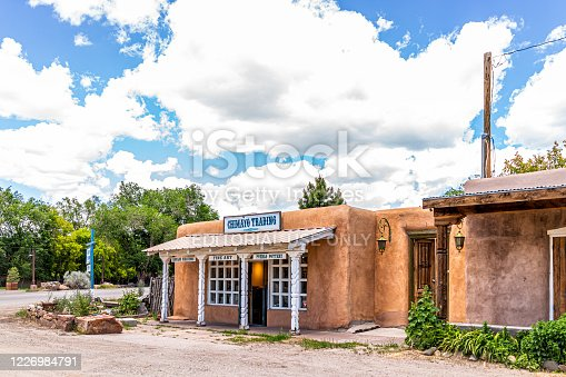 Ranchos de Taos, USA - June 19, 2019: Famous St Francic Plaza in New Mexico with Taos trading post store selling souvenirs chimayo sign