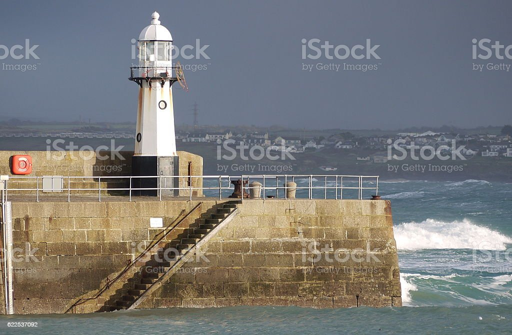 St Ives pier and lighthouse against stormy seas;Cornish resorts. stock photo