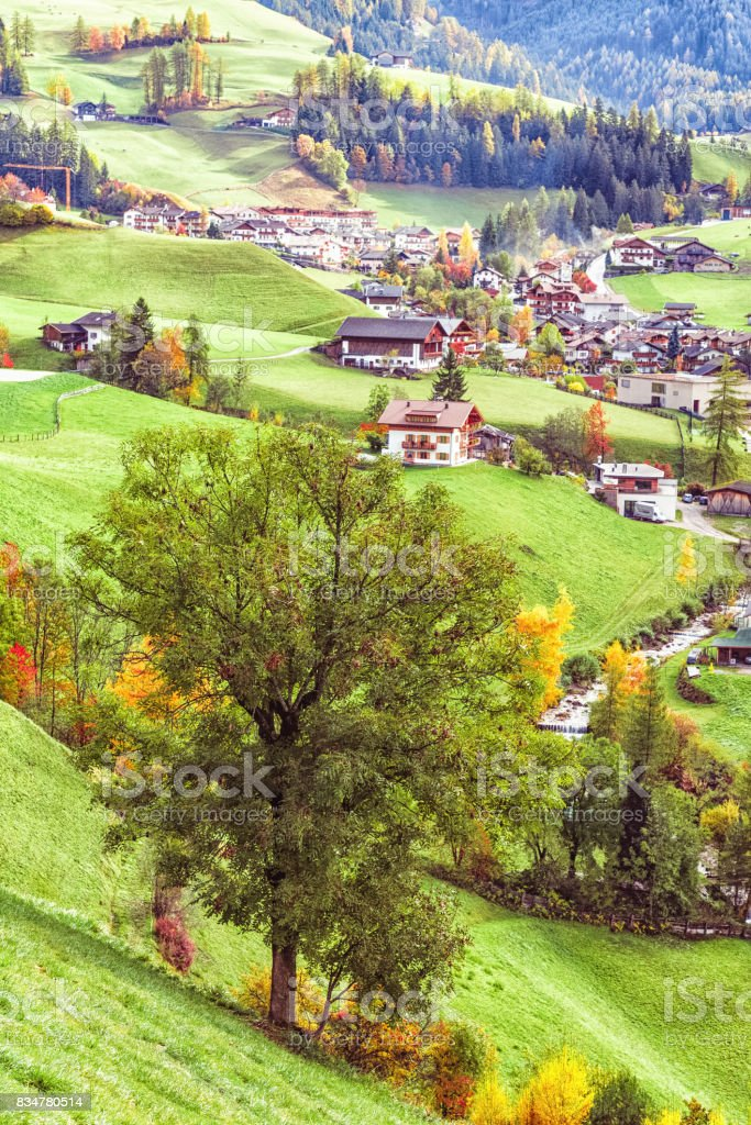 St Johann Church, Santa Maddalena, Val Di Funes, Dolomites, Italy. Beautiful view of idyllic autumn forest with baroque Church of St. Johann of Nepomuk  on a sunny day in the Dolomites, South Tyrol. stock photo