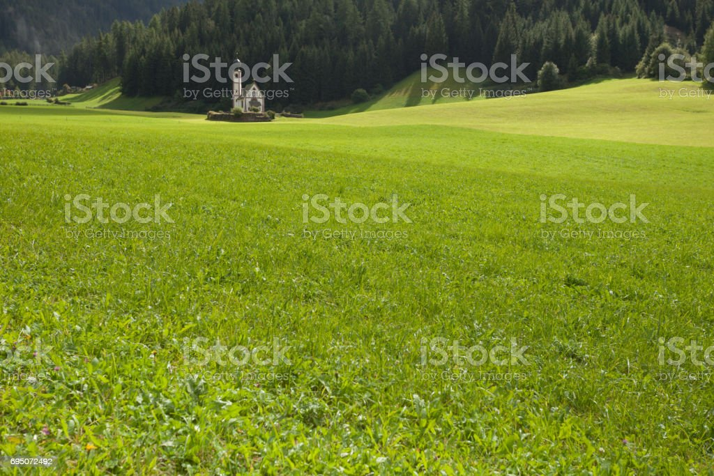 St. Johann little church among a wide green meadow in St. Magdalena , Val di Funes stock photo