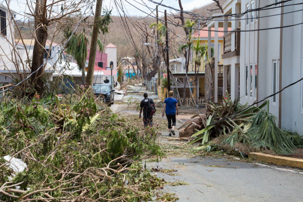 St John, hurricane Irma destruction on road Cruz Bay, St John, US Virgin Islands - Sept 08, 2017: Aftermath of Hurricane Irma, St John, People walking past recently cleared hurricane destruction in downtown Cruz Bay, 2 days after storm. Irma was a devastating cat 5 hurricane that hit St John with sustained winds of 185 mph and gusts well above 200 mph 2017 stock pictures, royalty-free photos & images