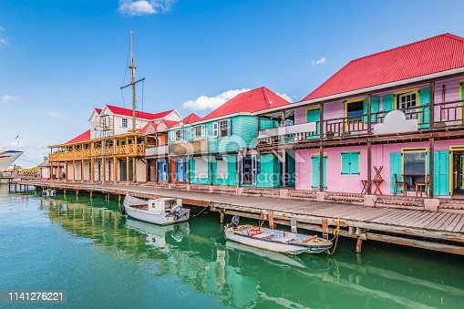 Bright image with colorful houses and shops along the waterfront at the port of St John`s, Antigua and Barbuda, Caribbean. Popular cruise destination.