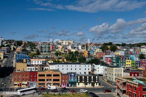 Brightly colored houses, known as Jelly Bean Row, march toward the hill overlooking St, John's, Newfoundland in a early morning shot with tourist disembarking to catch the tour bus