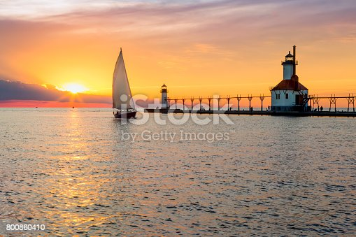 istock St. Joseph Lighthouse and Sailboat Solstice Sundown 800860410