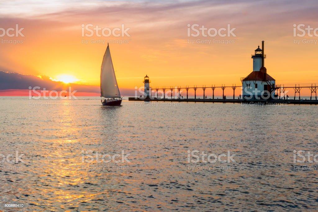 St. Joseph Lighthouse and Sailboat Solstice Sundown stock photo