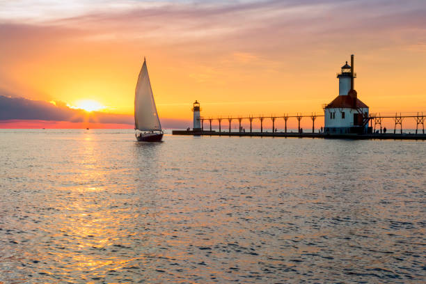 st. joseph lighthouse and sailboat solstice sundown - lake michigan stock pictures, royalty-free photos & images