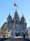 Red China flag in front of the facade. Christmas tree and decorations at the entrance to the church