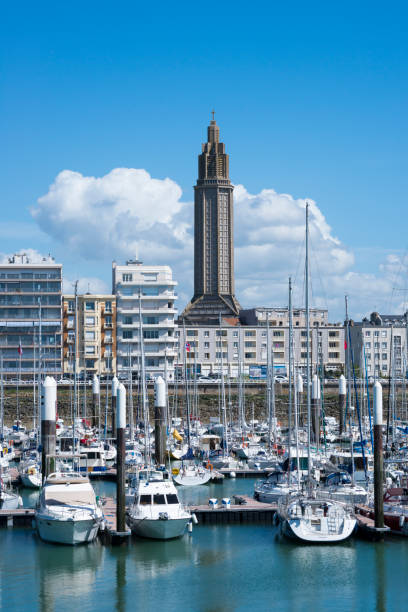 St. Joseph's Church in Le Havre, France The tower of St. Joseph's Church rises behind a marina in Le Havre, France. The city, largely destroyed by bombing during the Second World War, was rebuilt according to the plan of a team headed by Auguste Perret, from 1945 to 1964. Le Havre was designated a UNESCO World Heritage Site in 2005. le havre stock pictures, royalty-free photos & images