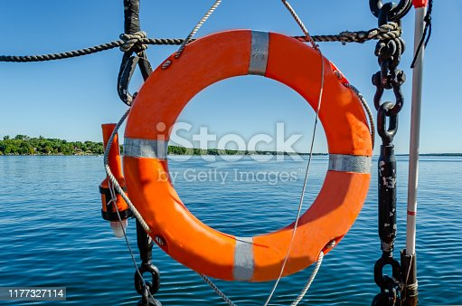 St. Lawrence River coastline and blue sky viewed through a Tall Ship's orange life preserver