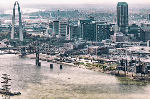 The Gateway to the West Arch and skyline of St. Louis, Missouri along the banks of the mighty Mississippi River shot from an altitude of about 600 feet over the river desaturated and toned in for a retro type feel.