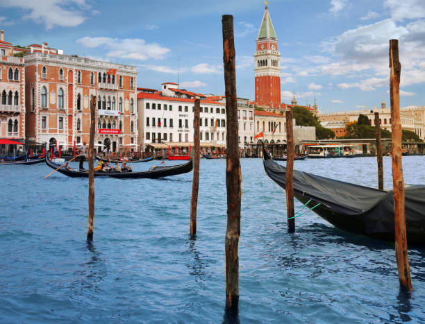St Mark's Campanile across Grand Canal and gondola with tourists in Venice, Italy stock photo
