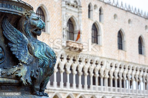 St Mark`s Square or Piazza San Marco, Venice, Italy. Detail with bronze sculpture of winged lion, symbol of Venice. Doge`s Palace in the background. Beautiful Renaissance architecture of Venice.