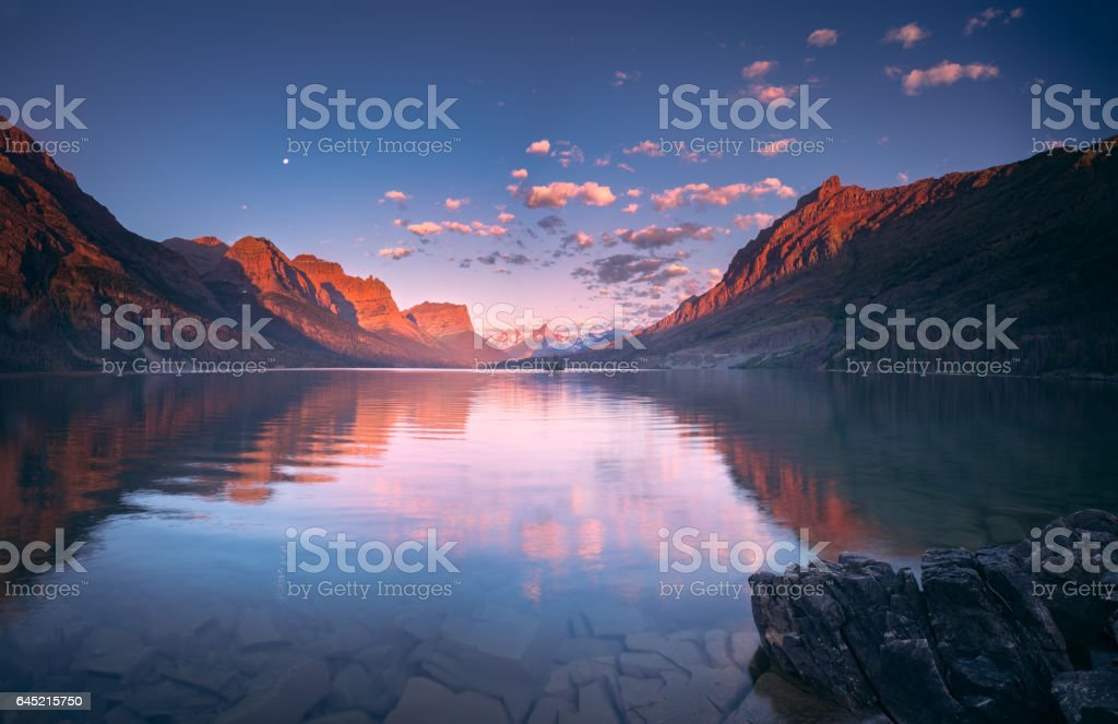 St Mary Lake in early morning with moon stock photo