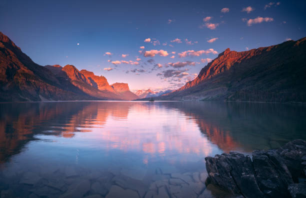 st mary lake in early morning with moon - st. mary lake stock pictures, royalty-free photos & images