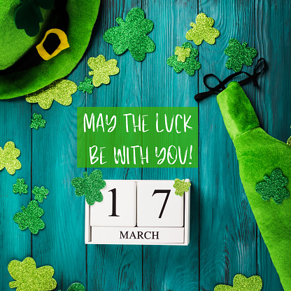 St Patrick Day dark green wooden rustic background with shamrocks and leprechaun costume accessories, date march 17 on vintage wooden calendar. May the luck be with you text quote