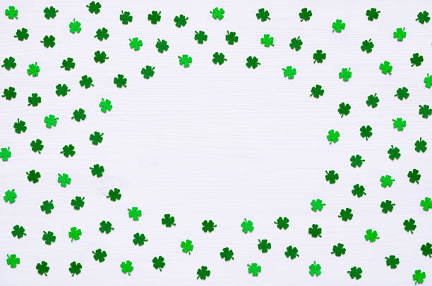 st patrick's day background with green quatrefoils on white background - happy st. patricks day stock photos and pictures