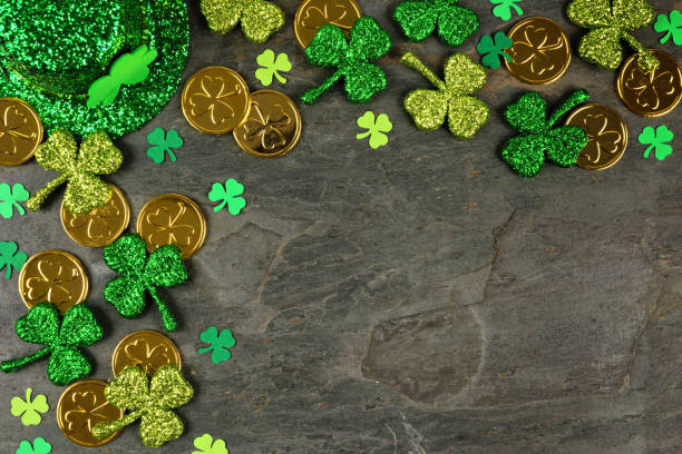 St Patricks Day corner border of shamrocks, gold coins & leprechaun hat over a dark background stock photo