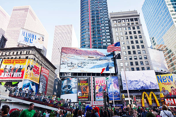 st patrick's day crowds in times square - mamma mia stock photos and pictures