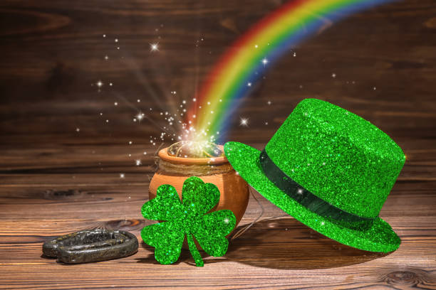 st patricks day decoration with magic light rainbow pot full gold coins, horseshoe, green hat and shamrock on vintage wooden background, close up - st patricks days stock photos and pictures