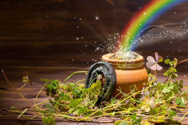 st patricks day decoration with magic light rainbow pot full gold coins, horseshoe and shamrocks on vintage wooden background, close up - luck of the irish stock photos and pictures