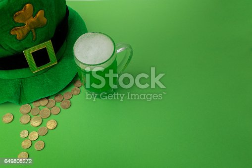 1124676977 istock photo St Patrick's Day green beer with shamrock, pot with gold coins, horseshoe and Leprechaun hat against green background 649808272