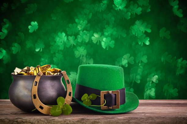 St Patrick's Day hat and pot with gold coins on green twinkling bokeh background St Patrick's Day hat and pot with gold coins on green twinkling background st patricks day stock pictures, royalty-free photos & images
